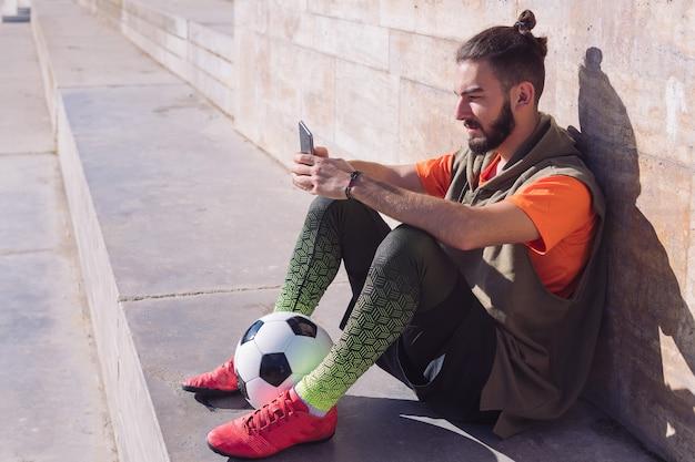 Descanso del jugador de fútbol consultando su teléfono móvil