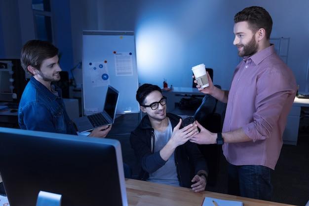 Descanso del trabajo. programadores masculinos atractivos alegres que se miran y sonríen mientras se toman un descanso del trabajo
