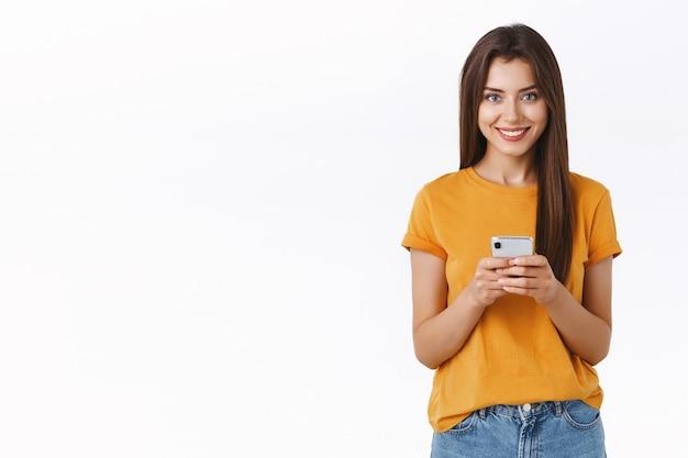 Descarada, feliz y guapa mujer con camiseta amarilla, sosteniendo la cámara con apariencia de teléfono inteligente complacida y alegre, comprando en línea, descarga la aplicación móvil para editar fotos y publicar en la red social