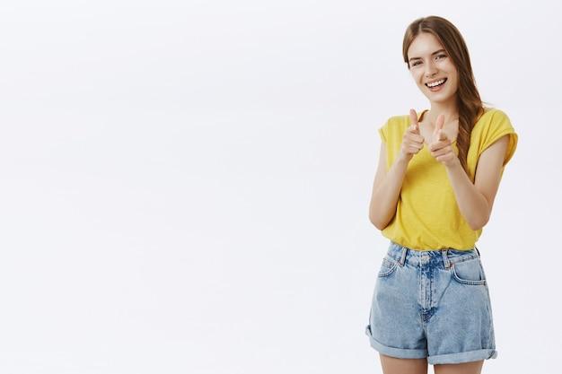 Descarada niña sonriente señalando con el dedo, tienes este gesto, alabando la buena elección