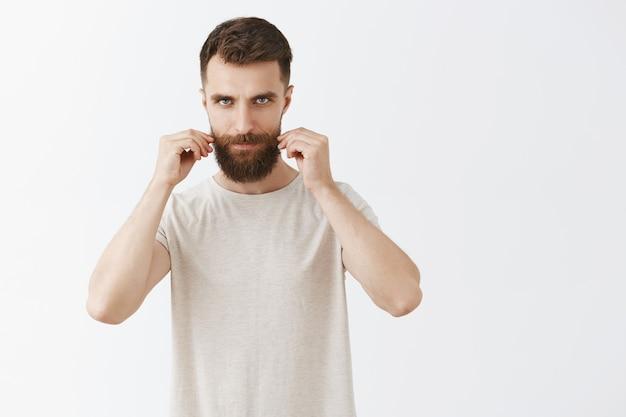Descarado barbudo barbudo posando contra la pared blanca