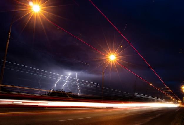 Descargas de rayos en el cielo nocturno sobre el fondo de la carretera