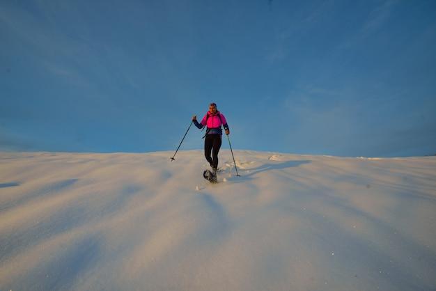 Descenso con raquetas de nieve. una mujer joven sola
