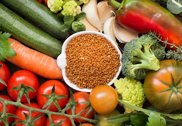 Descocina mijo marrón en un recipiente con vista superior de verduras