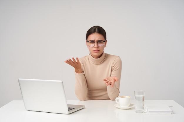Desconcertada joven atractiva mujer de cabello oscuro vestida con poloneck beige sentado a la mesa en la oficina moderna, teniendo una conversación tensa y levantando las manos emocionalmente, aisladas sobre la pared blanca