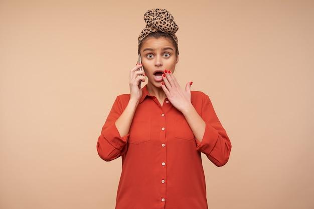 Desconcertada joven atractiva mujer morena con diadema redondeando aturdida sus ojos verdes y levantando emocionalmente la mano a la boca mientras escucha noticias sorprendentes en el teléfono