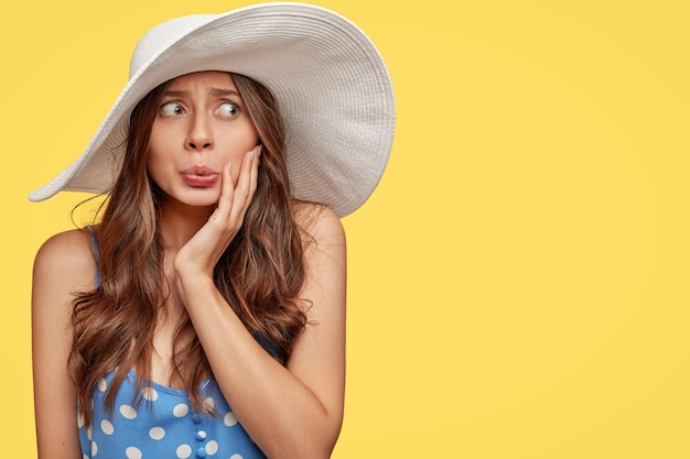 Desconcertada joven nerviosa con sombrero de verano de moda, presiona los labios y mira misteriosamente a un lado, mantenga la mano en la mejilla