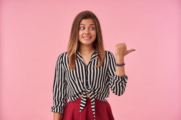Desconcertado joven dama de cabello castaño con peinado casual mostrando sus perfectos dientes blancos mientras mira confusamente a un lado, de pie contra rosa