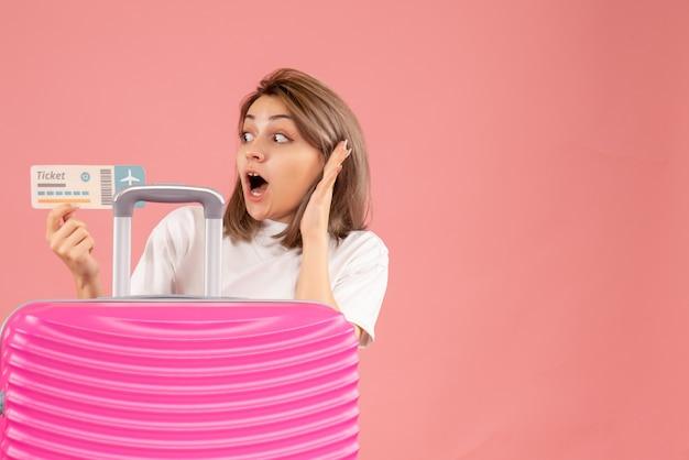 Desconcertado joven con maleta rosa con boleto en rosa