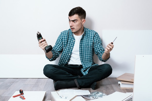 Desconcertado joven sentado en el suelo de la habitación con destornillador eléctrico y destornillador manual, problemas de selección, montaje de muebles