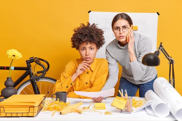 Desconcertado, preocupado, dos mujeres colaboran juntas para un proyecto de inicio común analizar la información del plano obtener asesoría de un entrenador a través de un teléfono inteligente tratar de encontrar la solución adecuada compartir opiniones creativas