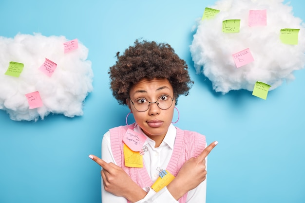 Desconcertado, vacilante, hábil trabajadora de negocios posa alrededor de coloridas pegatinas recordatorias vacila entre dos opciones usa gafas redondas aisladas sobre una pared azul