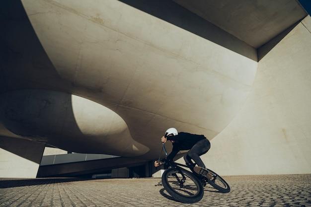 Desconocido bmx rider tomando una curva con una bicicleta debajo de un moderno parque de bicicletas.