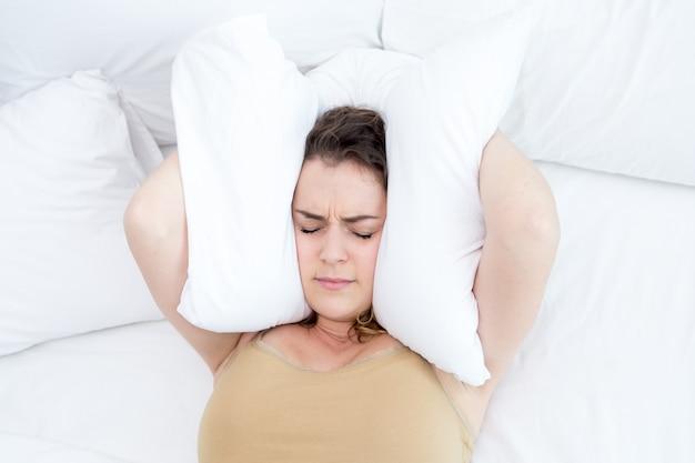 Descontenta, señora, cubriendo, orejas, almohada, cama