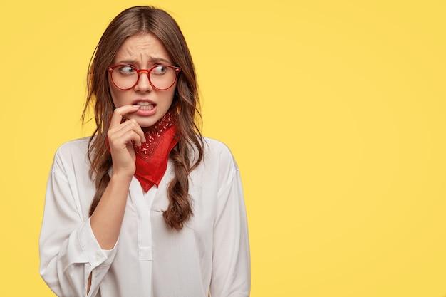 Descontento desconcertado chica mira ansiosamente con expresión preocupada a un lado, mantiene el dedo índice cerca de la boca, teme algo, usa pañuelo rojo en el cuello y camisa blanca, copia espacio para publicidad