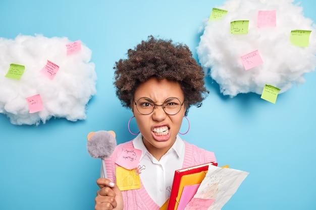 El descontento joven sonríe cara aprieta los dientes de la ira tiene fecha límite odia hacer los deberes se prepara para el examen usa gafas redondas sostiene bolígrafos papeles doblados aislados en la pared azul