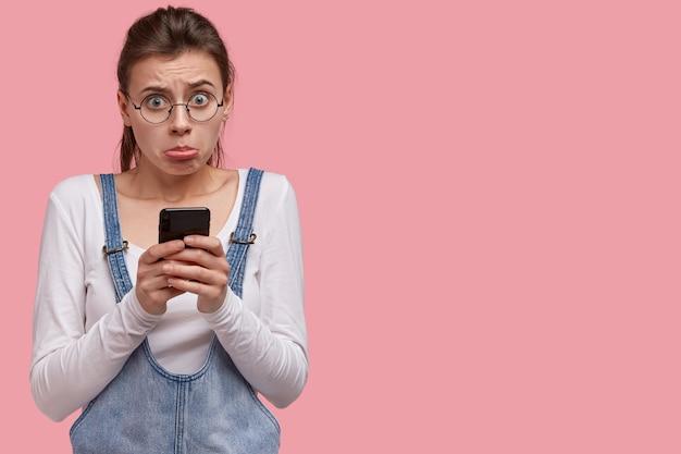 Descontento mujer caucásica frunce los labios, siente arrepentimiento e insatisfacción, usa teléfonos inteligentes actualizados para comunicarse
