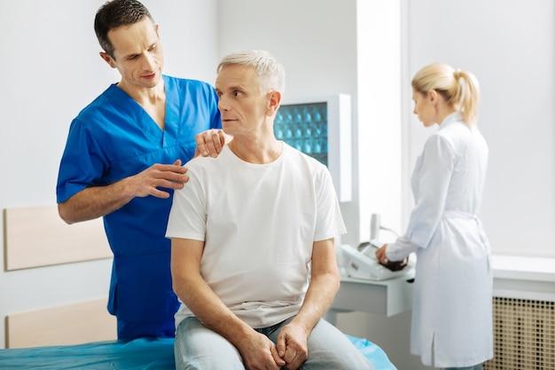 Describe tus sentimientos. hombre guapo inteligente de pie detrás de su paciente y tocando su hombro mientras le pide al dobladillo que describa lo que siente