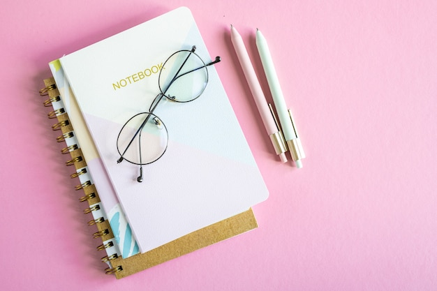 Descripción general de la mesa rosa con pila de cuadernos, anteojos y dos bolígrafos sin gente alrededor