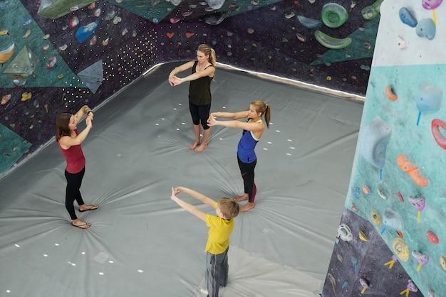 Descripción general de tres aprendices que estiran los brazos frente al pecho mientras repiten el ejercicio después de su instructor en el gimnasio