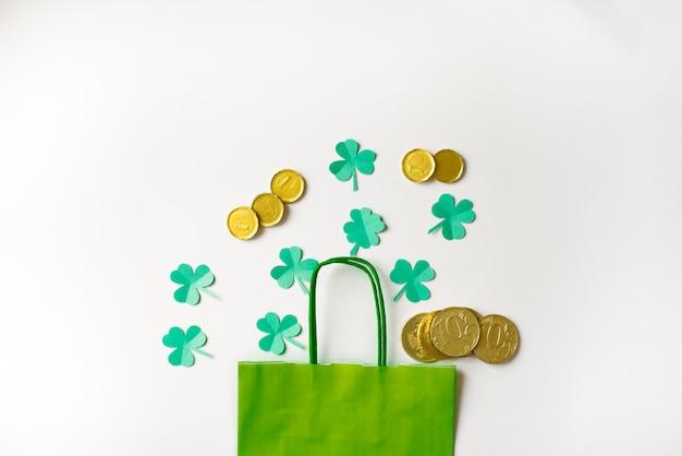 Descuentos para el día de san patricio. bolsa de papel verde y hojas de trébol de papel con monedas de oro sobre un fondo blanco.