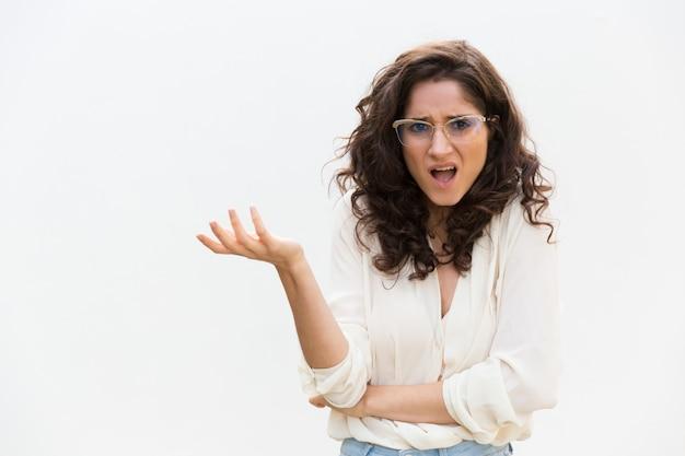 Descuidada mujer perpleja con gafas encogiéndose de hombros
