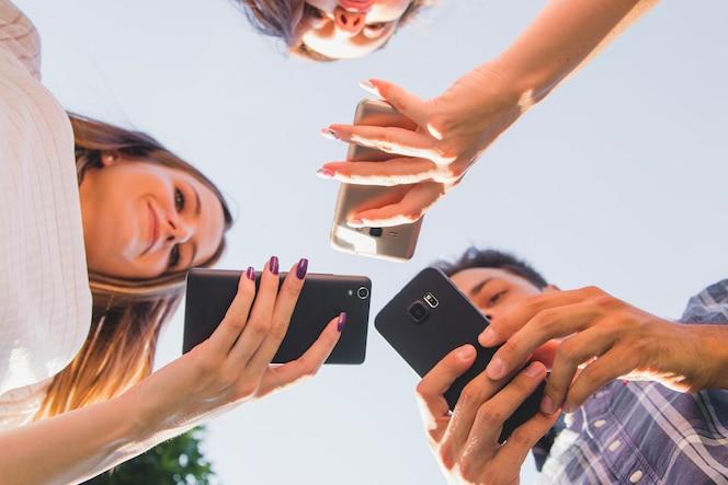 Desde abajo vista de los adolescentes con teléfonos inteligentes