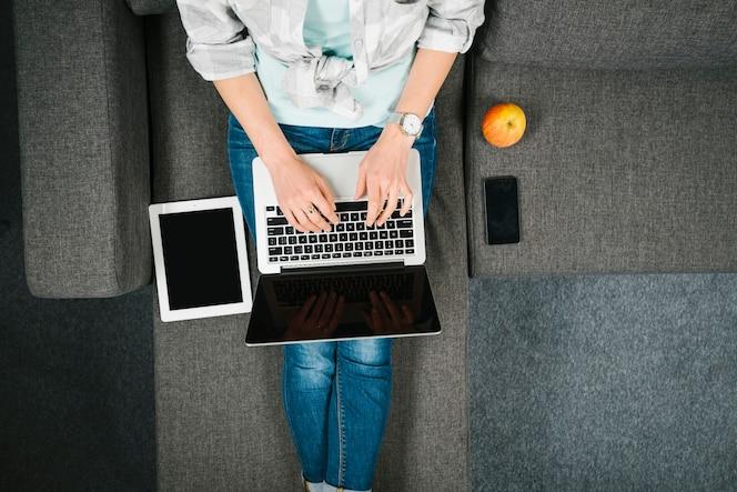 Desde arriba, la mujer busca la computadora portátil en el sofá