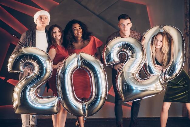 Deseando bien. grupo de hermosas jóvenes amigos con números inflables en manos celebrando el nuevo año 2020