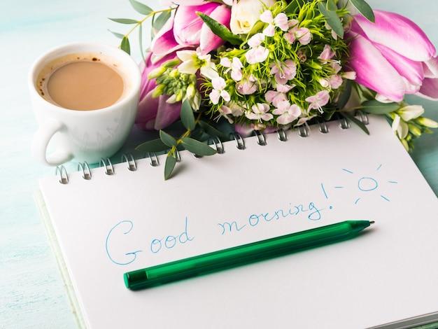 Deseando buenos días escritos a mano en página de cuaderno y taza de café.