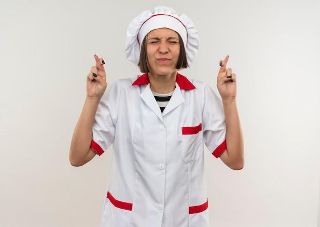 Deseando joven cocinera en uniforme de chef con los dedos cruzados y los ojos cerrados aislado sobre fondo blanco con espacio de copia