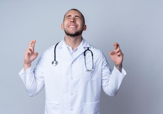 Deseando joven médico con bata médica y estetoscopio alrededor de su cuello haciendo gesto de dedos cruzados con los ojos cerrados aislado sobre fondo blanco con espacio de copia