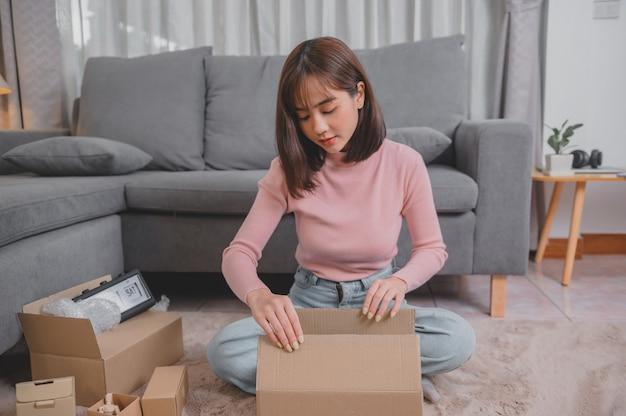Desempaque el paquete y abra el paquete cuando compre en línea y realice una buena entrega. estilo de vida de la mujer asiática en la sala de estar en casa. distanciamiento social y nueva normalidad.