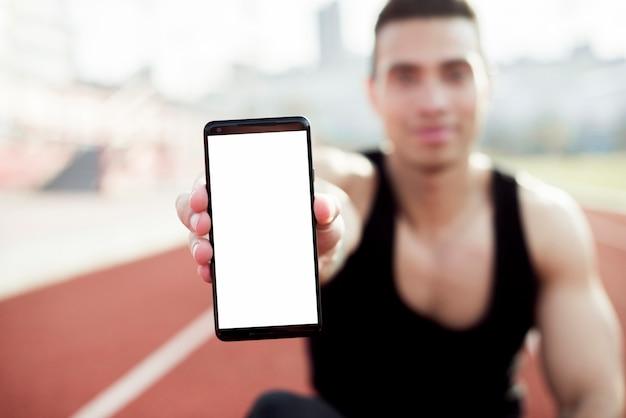 Desenfocado atleta masculino joven que muestra la pantalla del teléfono móvil hacia la cámara