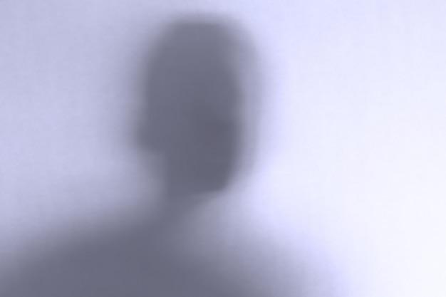 Desenfocado cara de fantasma aterrador detrás de un cristal blanco