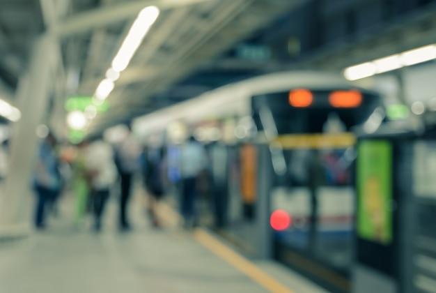 Desenfocado de una cola de pasajeros en el fondo de la estación de tren interior