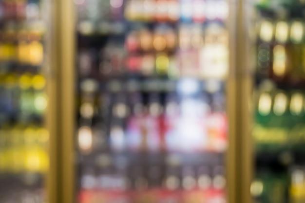 Desenfoque de botellas de bebida fría que se muestran en los estantes del congelador frío en el supermercado o tienda de conveniencia