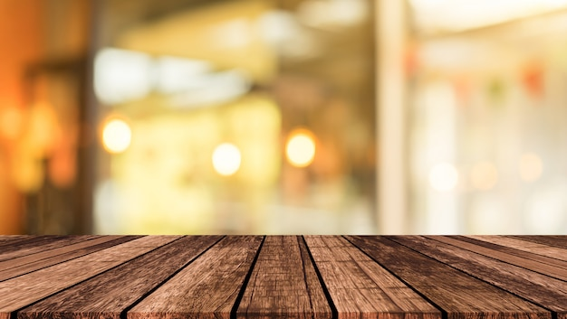 Desenfoque de color café claro del restaurante con fondo de mesa de madera marrón vintage