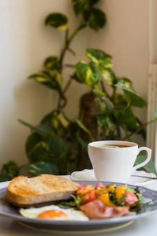 Desenfoque de desayuno y té en la mesa frente a las plantas