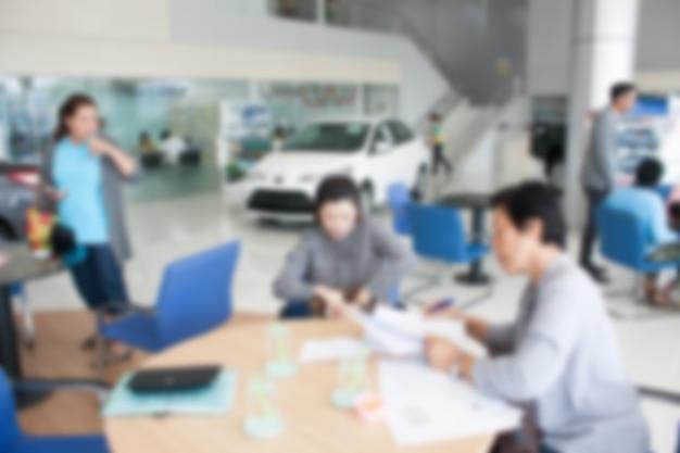 Desenfoque de foto de la sala de exposición de automóviles con el vendedor y los clientes