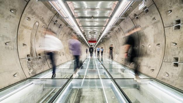 Desenfoque de movimiento de los asiáticos caminando en la pasarela del túnel del metro