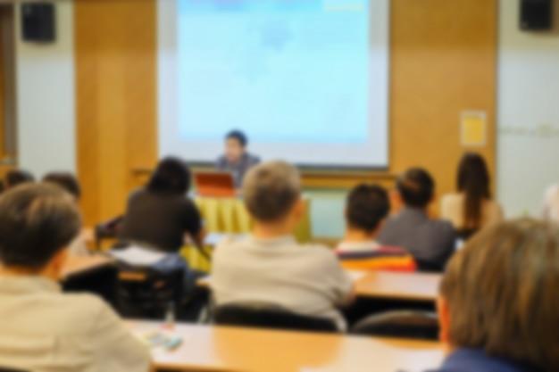 El desenfoque de movimiento del orador presenta un proyecto con una audiencia en una sala de reuniones