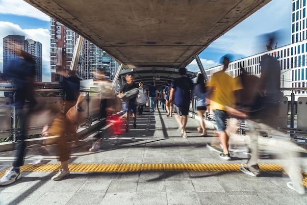Desenfoque de movimiento de personas asiáticas abarrotadas caminando en una pasarela pública elevada