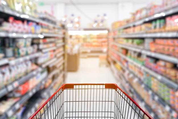 Desenfoque del pasillo del supermercado con carrito de compras rojo vacío
