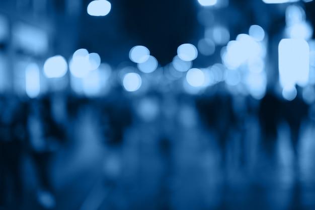Desenfoque a las personas que hacen compras en el mercado callejero local con bokeh azul y luz de sol resumen antecedentes.