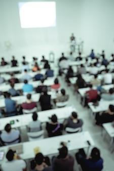 Desenfoque de personas en sala de conferencias.
