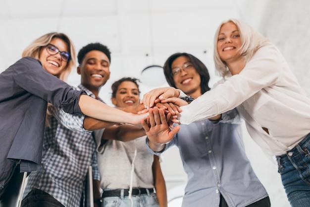 Desenfoque de retrato de equipo de jóvenes oficinistas con las manos en foco. foto interior de estudiantes internacionales riendo con elegantes atuendos apoyándose entre sí antes de los exámenes.