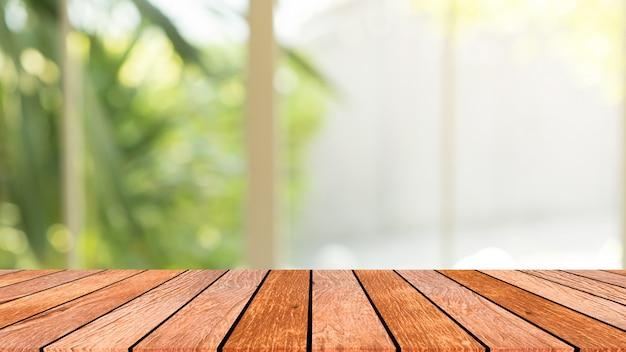 Desenfoque de la vista del jardín desde la ventana con luz de la mañana con la perspectiva de la mesa de madera para el fondo