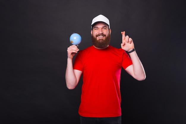 Deseo viajar por el mundo, feliz hipster barbudo cruzando los dedos y sosteniendo el globo