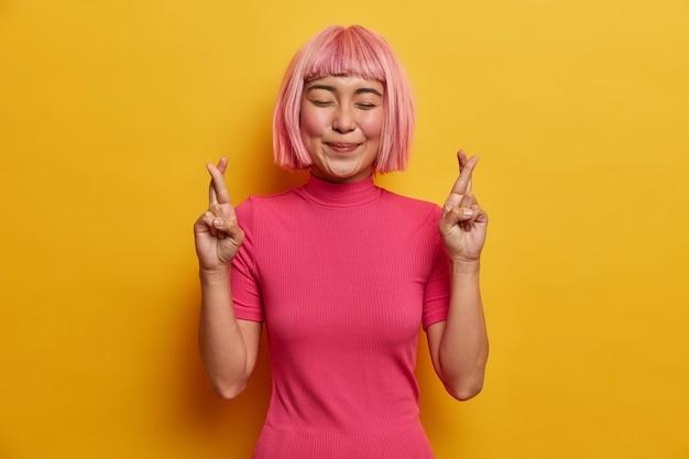 Deseosa mujer asiática positiva cruza los dedos antes de eventos importantes sonríe felizmente con los ojos cerrados tiene grandes esperanzas en algo mejor